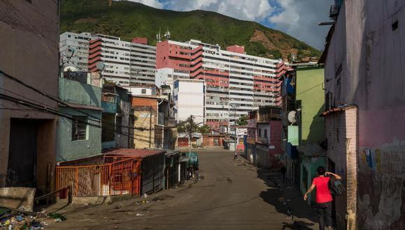Ramiro corre hacia su casa mientras suenan disparos en La Vega, el 7 de junio de 2021, en Caracas, Venezuela. (EFE/ Miguel Gutiérrez).
