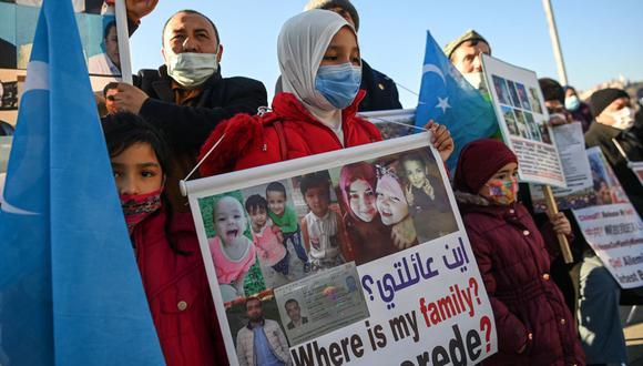 Miembros de la minoría uigur sostienen pancartas mientras se manifiestan para pedir noticias de sus familiares y expresar su preocupación por la ratificación de un tratado de extradición entre China y Turquía, el 22 de febrero de 2021 cerca del consulado de China en Estambul. (Foto de Ozan KOSE / AFP).