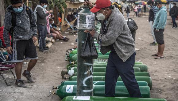 Un hombre mueve un balón de oxígeno en Villa El Salvador, en abril de 2021. (Foto: ERNESTO BENAVIDES / AFP)