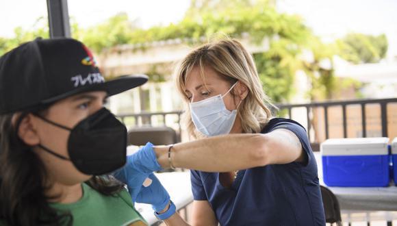 Una enfermera administra una dosis de la vacuna Pfizer Covid-19 a una estudiante de secundaria en Long Beach, Estados Unidos. (Foto de Patrick T.FALLON / AFP).