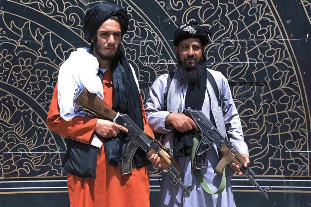 Dos combatientes talibanes montan guardia frente a la oficina del gobernador provincial en Herat, Afganistán, el 14 de agosto de 2021. (Foto: AFP).