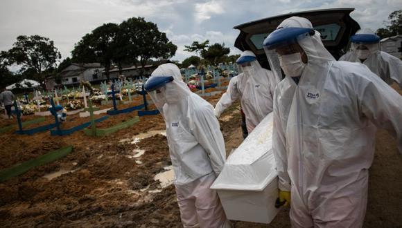 Trabajadores entierran a una persona fallecida por covid-19, en el cementerio público Nossa Senhora Aparecida en Manaos, Amazonas (Brasil). Raphael Alves/Archivo