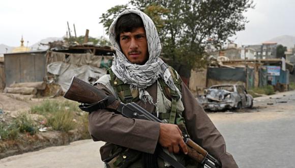 Un combatiente talibán monta guardia cerca de un automóvil dañado después de que se dispararan múltiples cohetes en Kabul. (Foto: WAKIL KOHSAR / AFP).