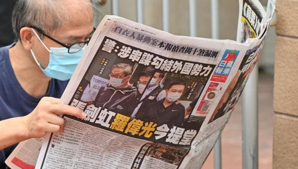 Esta foto tomada el 19 de junio de 2021 muestra a una persona leyendo el periódico Apple Daily frente a un tribunal de justicia en Hong Kong, luego de que los dos empleados del diario fueran arrestados. (Foto de Peter PARKS / AFP).