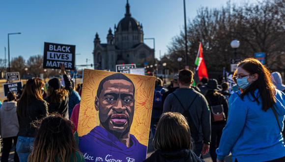 Dos niños sostienen un cartel de George Floyd mientras los manifestantes se paran cerca del Capitolio del estado de Minnesota, Estados Unidos, el 19 de marzo de 2021. (Foto de Kerem Yucel / AFP).