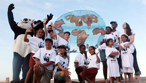 Los miembros del Fondo Mundial (WWF) para la Naturaleza entregan un planeta Tierra simbólico hecho de alambre y abalorios a los niños locales en la playa de Durban.  (AFP/RAJESH JANTILAL).