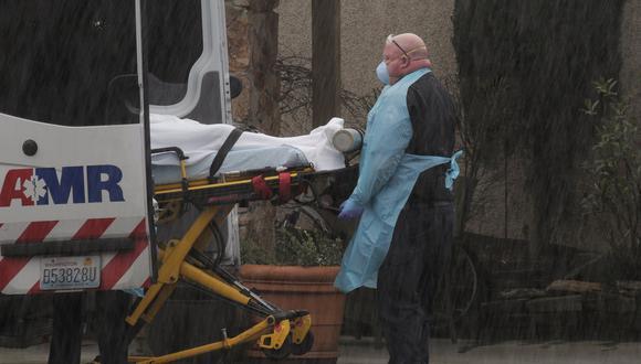 Los médicos transportan a un paciente bajo una fuerte lluvia a una ambulancia en el Life Care Center de Kirkland, un centro vinculado a varios casos confirmados de coronavirus en estados Unidos. (REUTERS / David Ryder).