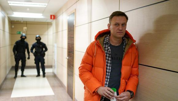 Esta foto de archivo tomada el 26 de diciembre de 2019 muestra al líder de la oposición rusa Alexei Navalny de pie cerca de los agentes del orden en un pasillo de un centro de negocios en Moscú. (AFP/Dimitar DILKOFF).