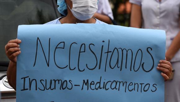 """Una trabajadora de salud sostiene un cartel que dice """"Necesitamos más medicamentos y suministros médicos para los pacientes"""" mientras participa en una protesta contra la corrupción en Paraguay. (Foto de Norberto DUARTE / AFP)."""