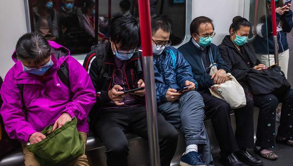 Personas con máscaras viajan en tren el primer día del Año Nuevo Lunar de la Rata en Hong Kong, como medida preventiva después de un brote de coronavirus de Wuhan. (Foto: AFP)