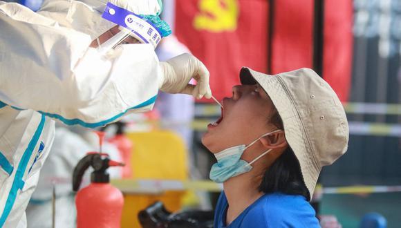 Esta foto tomada el 1 de agosto de 2021 muestra a una persona siendo sometida a la prueba de coronavirus covid-19 en Yangzhou, en la provincia oriental de Jiangsu, en China. (Foto de STR / AFP).