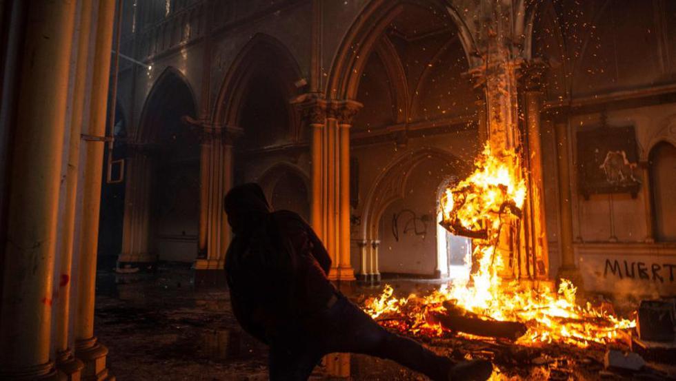 Un manifestante prende fuego dentro de la iglesia de San Francisco de Borja durante enfrentamientos con la policía antidisturbios en la conmemoración del primer aniversario del levantamiento social en Chile, mientras el país se prepara para un referéndum histórico. (AFP / MARTIN BERNETTI).