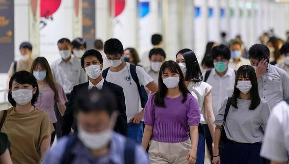 Las personas usan máscaras faciales en su camino de regreso a casa en Tokio tras su jornada laboral. (EFE / EPA / KIMIMASA MAYAMA).