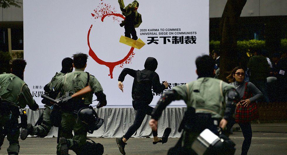 La policía antidisturbios persigue a un hombre enmascarado durante una manifestación que exige la democracia electoral y llama al boicot al Partido Comunista Chino y a todas las empresas que lo respaldan en Hong Kong. (Foto: AP)