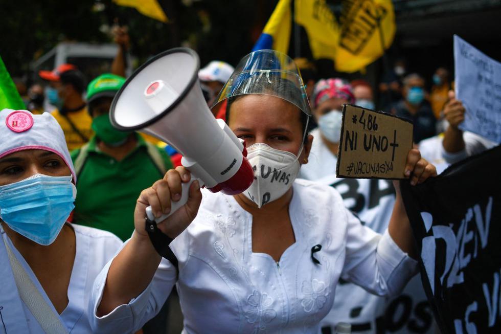 """""""SOS. Vacunas ya"""", decía este sábado uno de los carteles en una protesta de médicos y enfermeras en Venezuela en exigencia de vacunas contra el coronavirus, movilización acompañada por dirigentes políticos y activistas de oposición. (Texto y foto: AFP)."""