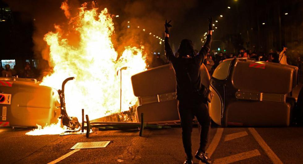 Un manifestante gesticula frente a contenedores de basura en llamas durante los enfrentamientos con las fuerzas policiales regionales catalanas Mossos d'Esquadra después de una manifestación contra el encarcelamiento del rapero español Pablo Hasel en Barcelona. (AFP / Pau BARRENA).