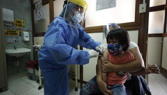Edelmira Rojas abraza a su hijo para que este reciba la vacuna contra la varicela y contra la influenza. En el INSN de Breña vacunan de lunes a sábado a todos los niños menores de 5 años. (Foto: César Campos / @photo.gec)