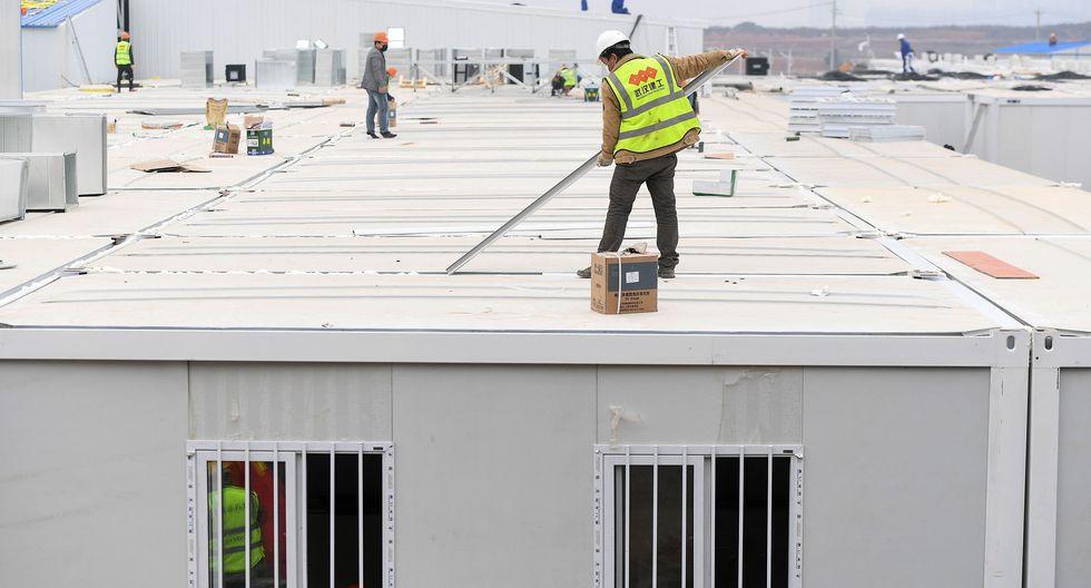 Los empleados chinos trabajan en el techo del Hospital Huoshenshan. (AFP).