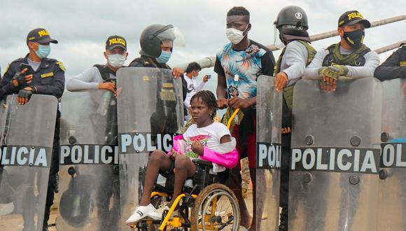 La policía abre paso a una mujer en silla de ruedas mientras una multitud de migrantes de varias nacionalidades, entre ellos haitianos, intentan cruzar al Perú por el Puente de la Amistad en la frontera con Brasil. (Foto: Radio Madre de Dios / AFP).
