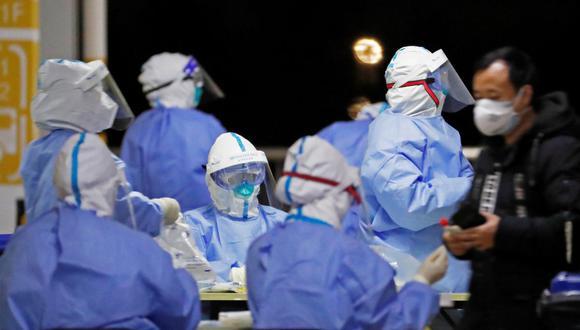 Trabajadores de la salud con trajes de protección realizan pruebas de detección de coronavirus COVID-19 en el personal del aeropuerto de Pudong en Shanghai. (Foto: AFP).
