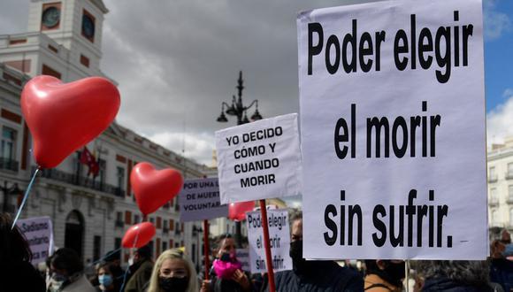 """La gente sostiene pancartas que dicen """"Elegir morir sin sufrir"""" y """"Yo decido cuándo y cómo morir"""" durante una manifestación en apoyo a una ley que legaliza la eutanasia en España. (Foto de JAVIER SORIANO / AFP)."""