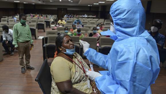 Un trabajador de la salud toma una prueba de hisopado de coronavirus a una mujer en Chennai, el pasado 22 de febrero de 2021, cuando los casos de COVID-19 en India superaron los 11 millones. (Arun SANKAR / AFP).