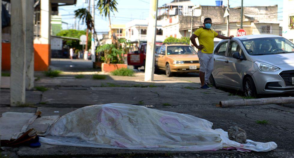 Un hombre mira el cuerpo de una persona que estuvo tres días fuera de una clínica en Guayaquil, el epicentro del coronavirus en Ecuador. (AFP / Pin de Marcos / Str).