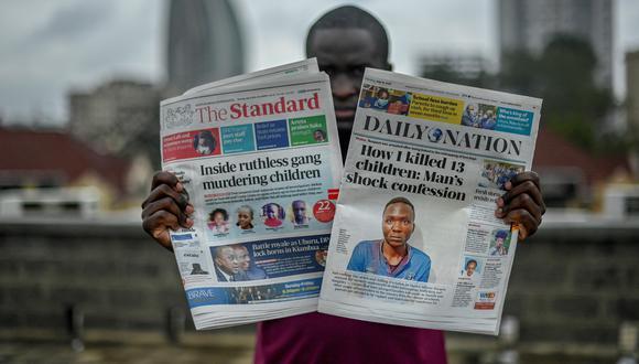 Un hombre sostiene los periódicos The Standard y Daily Nation que llevan titulares sobre el asesino Masten Milimo Wanjala, involucrado en la muerte de al menos 10 niños en Nairobi el 15 de julio de 2021.  (Foto: SIMON MAINA / AFP)