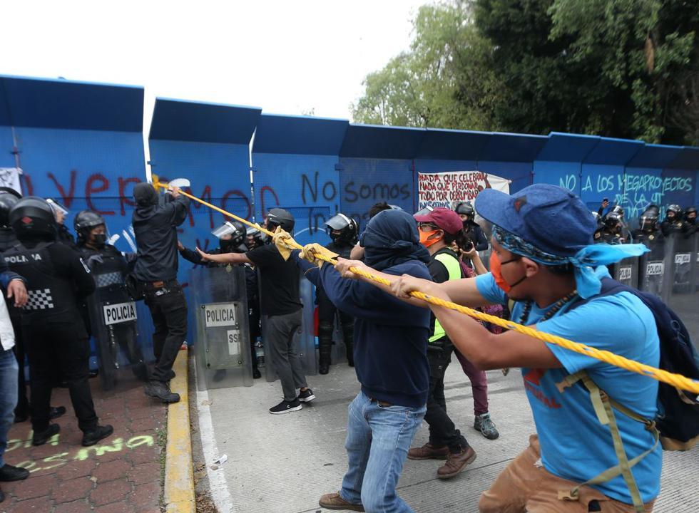 Manifestantes intentan derribar las barreras de acero que cercan el lugar en el que se ubica una estatua de Cristóbal Colón, en Ciudad de México. (EFE/Sáshenka Gutiérrez).