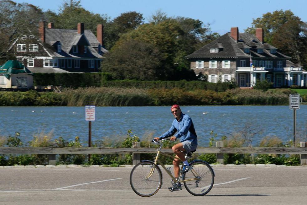 Un hombre anda en bicicleta cerca de la playa en Southampton, Nueva York. Las sombrillas de playa están en los garajes traseros cuando las temperaturas bajan, pero los neoyorquinos adinerados se quedan en los Hamptons más allá del verano, temerosos de la pandemia y el aumento de la delincuencia. (AFP / Kena Betancur).