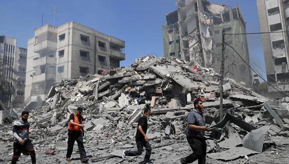 Gente revisando los escombros del edificio residencial Yazegi, destruido por un ataque aéreo israelí en Ciudad de Gaza, el domingo 16 de mayo de 2021. (AP Foto/Adel Hana).