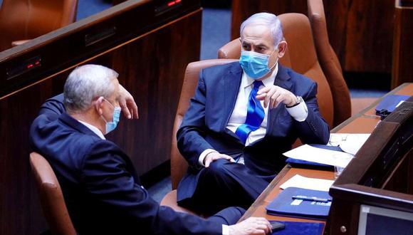 El primer ministro israelí Benjamín Netanyahu y Benny Gantz, líder centrista azul y blanco y socio de Netanyahu en su nuevo gobierno de unidad, usan máscaras mientras hablan durante una ceremonia de juramento del nuevo gobierno, en la Knesset, el parlamento de Israel. (Reuters/Amos Ben Gershon).