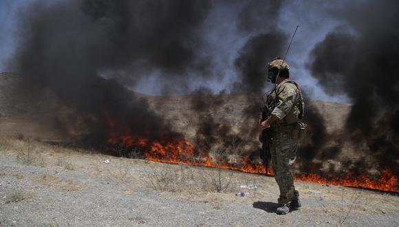 Imagen referencial. En Kabul, Afganistán, un miembro de las fuerzas de seguridad del país observa la incineración de drogas. EFE
