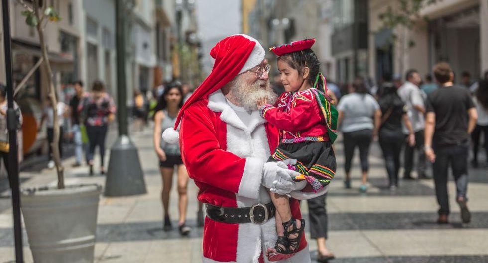 Genaro Aldón (73), conocido como el Papa Noel Mágico, le pide a la pequeña Aracely (3) su lista de deseos. Su madre, una vendedora en el Centro de Lima, dice que quiere muñecas.