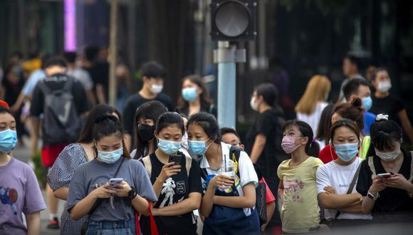 Personas que usan mascarillas para protegerse contra el coronavirus esperan para cruzar una intersección en Beijing. (Foto: AP / Mark Schiefelbein)