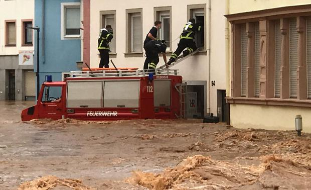 Firefighters on the roof of their vehicle enter a flooded house in the flood-ravaged Ehrong area of Trier, West Germany, on July 15, 2021.  (AFP).