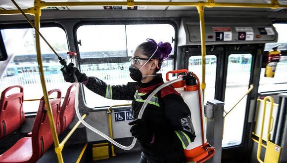 Una trabajadora desinfecta un bus de transporte público en Bogotá. El gobierno de Colombia decretó una cuarentena ante el avance del coronavirus. (AFP / Juan BARRETO).