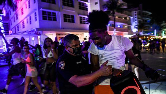 La policía de Miami Beach detiene a un hombre que lleva un parlante inalámbrico en Ocean Drive. (Foto de CHANDAN KHANNA / AFP).