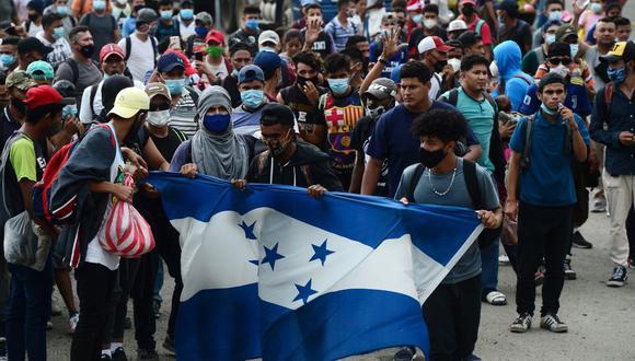 Migrantes hondureños sostienen una bandera de su país después de romper una cerca policial y entrar a Guatemala desde Corinto, Honduras, el 1 de octubre de 2020. (Foto de ORLANDO SIERRA / AFP).