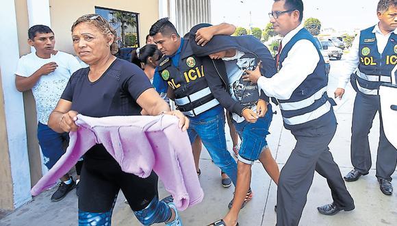 Esta mujer intenta cubrir el rostro de 'Giuseppi', adolescente retenido ayer en el Callao, cuando es trasladado a la sede del Poder Judicial. Lo acusan de haber asesinado a tres personas el año pasado. (Foto: Jessica Vicente / El Comercio)