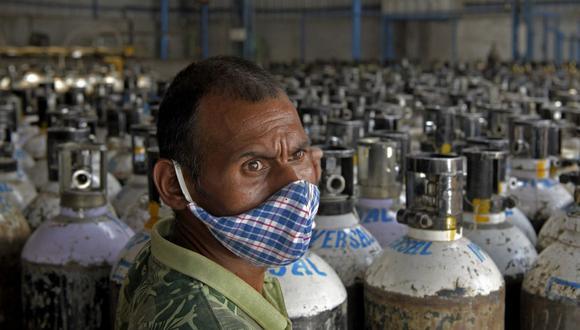 Un trabajador clasifica cilindros de oxígeno que se utilizan para pacientes de coronavirus Covid-19 antes de enviarlos a hospitales en Bangalore, India. (Foto de Manjunath Kiran / AFP).