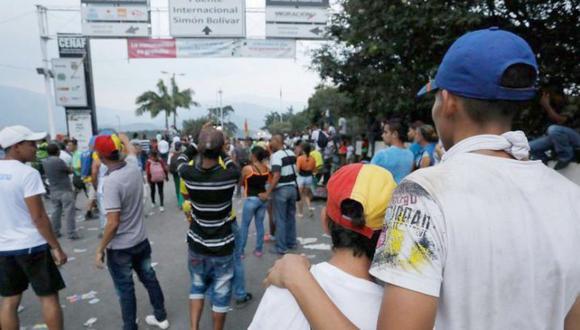 La mamá y su hijo, de espaldas, el sábado, en el puente fronterizo Simón Bolívar. (Foto: Carlos Ortega / El Tiempo de Colombia - GDA)
