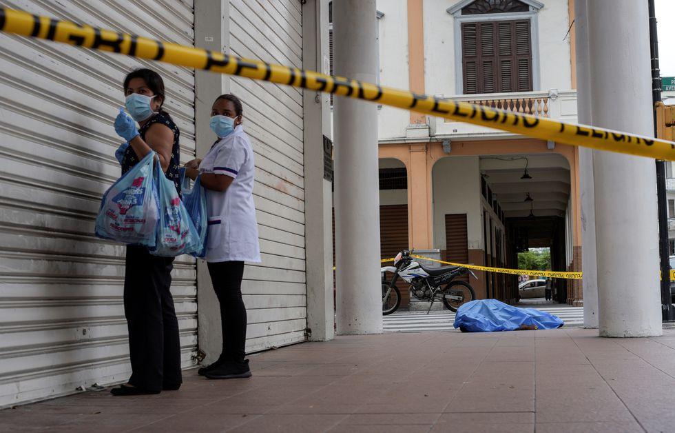 Una mujer parada junto al cadáver de un hombre que colapsó en la vereda durante el brote de coronavirus en la ciudad de Guayaquil, Ecuador. (Reuters)