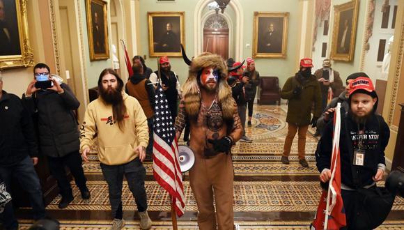 Los partidarios del presidente de los Estados Unidos, Donald Trump, incluido Jake Angeli (centro), un integrante de QAnon, ingresan al Capitolio el 6 de enero de 2021. (Foto de Saul LOEB / AFP).