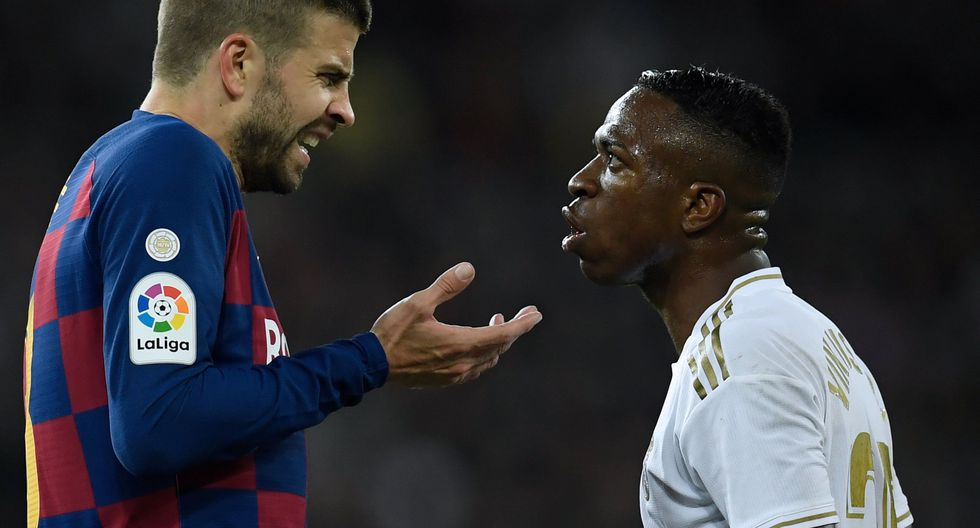 Barcelona's Spanish defender Gerard Pique (L) talks with Real Madrid's Brazilian forward Vinicius Junior during the Spanish League football match between Real Madrid and Barcelona at the Santiago Bernabeu stadium in Madrid on March 1, 2020. / AFP / OSCAR DEL POZO