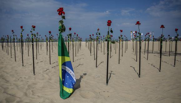 """Centenares de rosas rojas fueron """"plantadas"""" en la emblemática playa de Copacabana, en Río de Janeiro (Brasil), en memoria de las 500.000 personas fallecidas por la COVID-19 en Brasil, uno de los países del mundo más afectados por la pandemia. EFE/Antonio Lacerda"""
