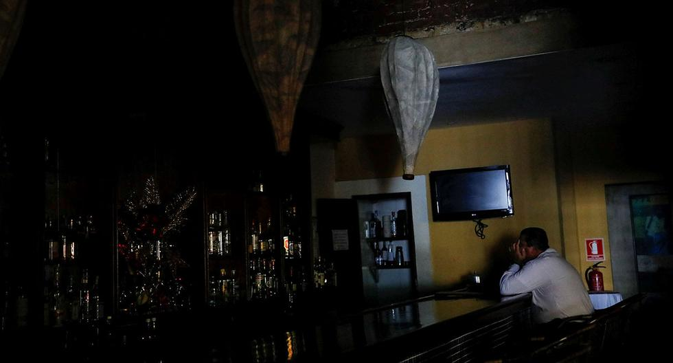A worker waits for clients at the bar of a restaurant, during a massive blackout in Caracas, Venezuela December 18, 2017. REUTERS/Carlos Garcia Rawlins