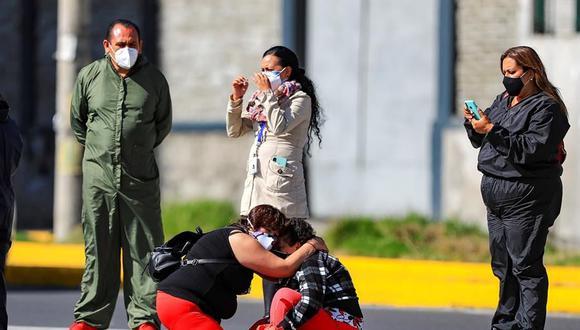 Familiares de pacientes diagnosticados con la COVID-19 esperan información en el hospital del Iess, en Quito (Ecuador). (EFE/José Jácome).