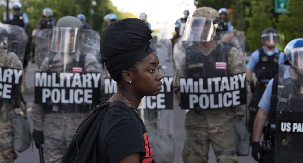 Una manifestante camina frente a una fila de miembros de la Policía Militar cerca de la Casa Blanca, donde este lunes hubo una protesta por el asesinato de George Floyd. (Foto por Jose Luis Magana / AFP).