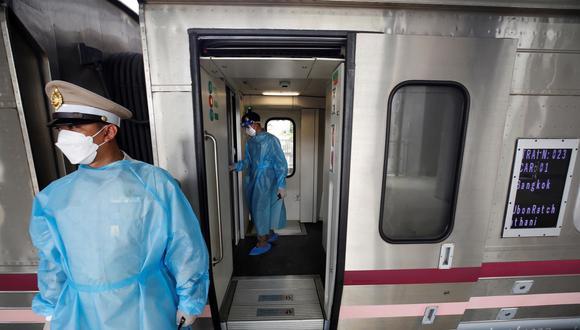La policía ferroviaria de Tailandia camina dentro de un tren de pasajeros mientras espera que los pacientes con coronavirus COVID-19 lleguen para abordar el transporte que los llevará de regreso a sus provincias. (EFE / EPA / NARONG SANGNAK).